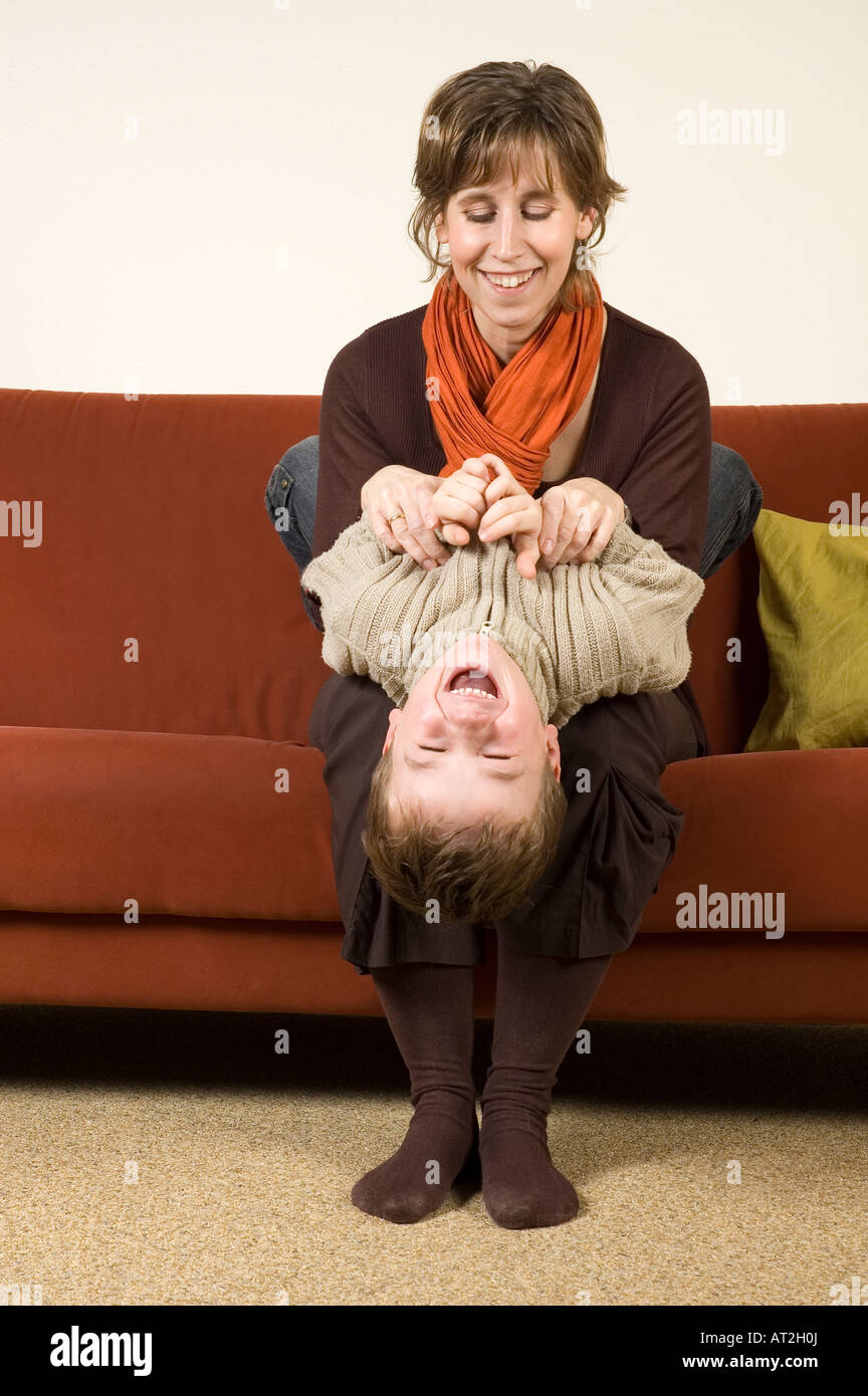 Mother playing with her son on the couch Nice family picture - Stock Image