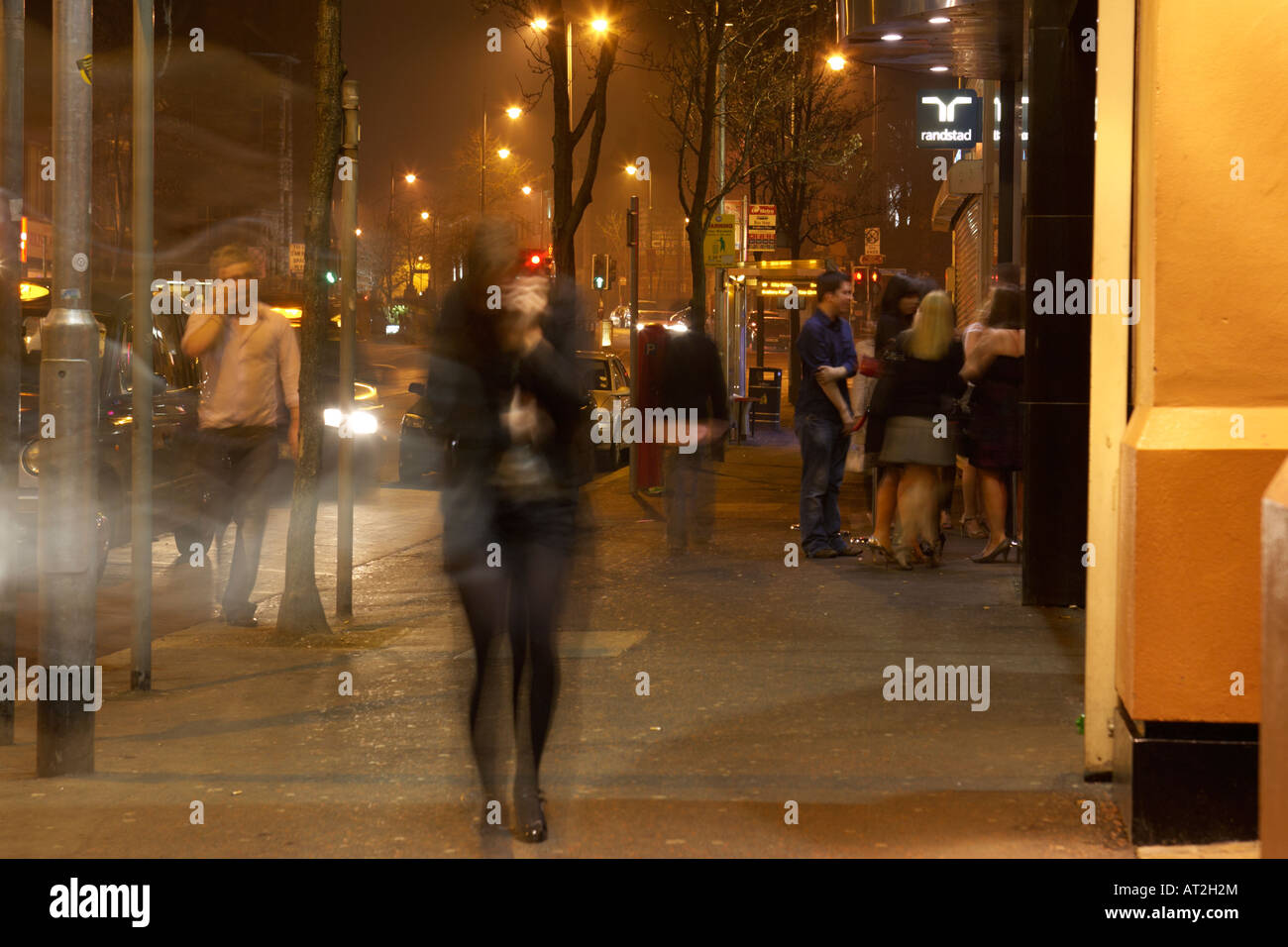 people nightclubbers walking past pubs and clubs on bradbury place belfast - Stock Image