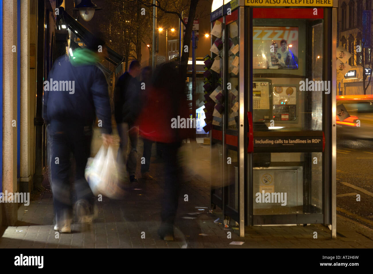 young man carrying shopping bags walk past telephone call box outside pub area bradbury place belfast - Stock Image