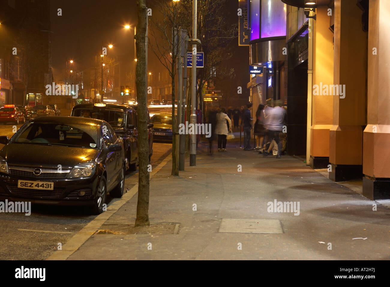people nightclubbers queuing on city street to get into pubs and clubs on bradbury place belfast - Stock Image
