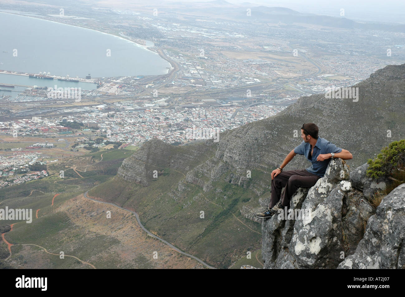 Solitary man looking over cape town from summit of Table Mountain South Africa - Stock Image