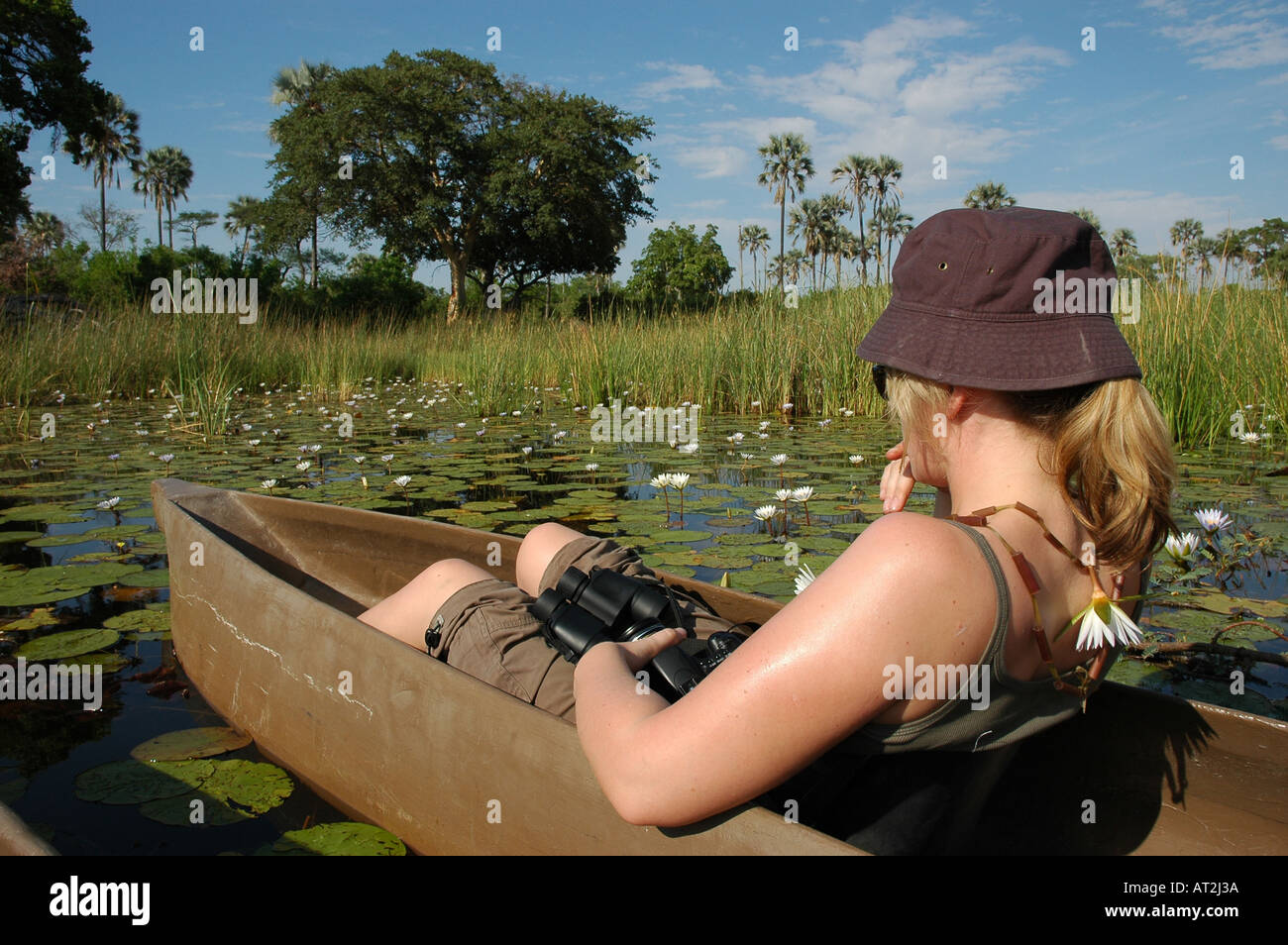 Female girl tourist in Mokoros on river near Tubu tree safari camp in Okavango Delta Botswana southern Afr - Stock Image