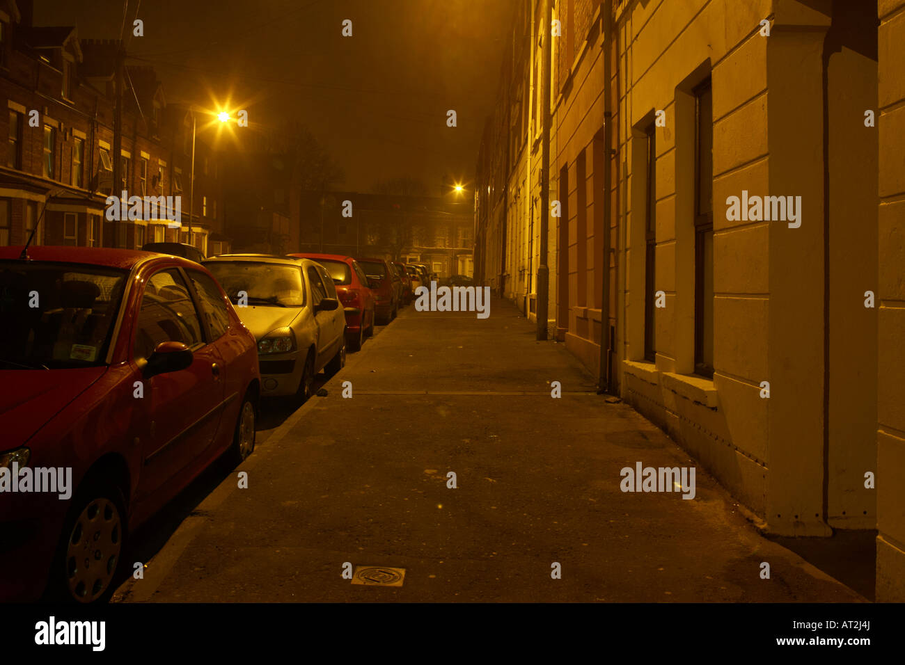 empty deserted footpath on dark nighttime street in Belfast - Stock Image