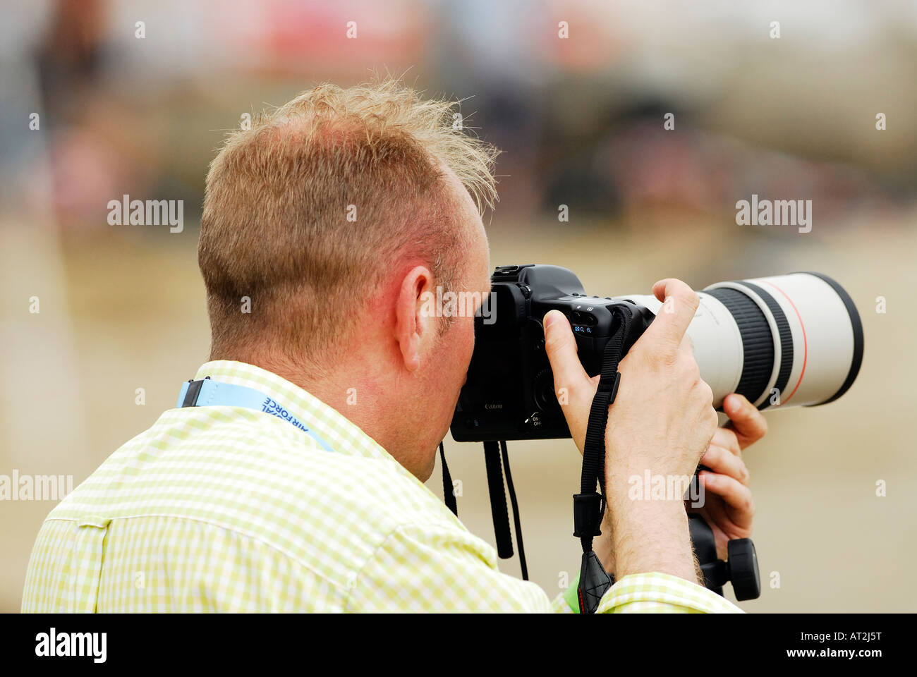a man photographer using a digital slr camera with a lon telephoto zoom lens attached taking a photograph picture Stock Photo