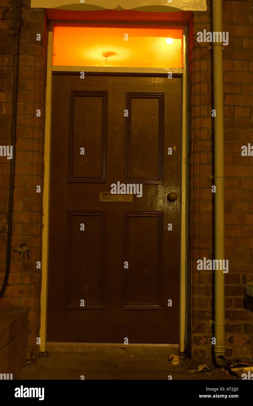 door in old red brick run down building with red light above doorway - Stock Image