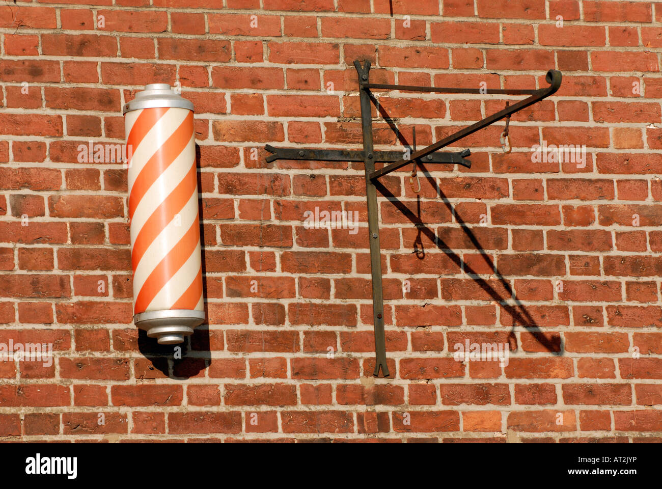 traditional barbers pole advertising hairdressers hair cutting services outside of an authentic old fashioned barbers - Stock Image