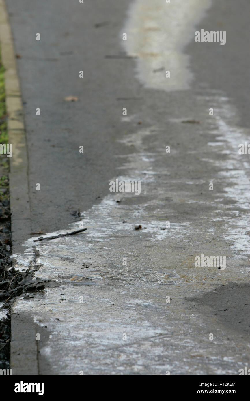 water leak frozen to ice on a public path in belfast - Stock Image