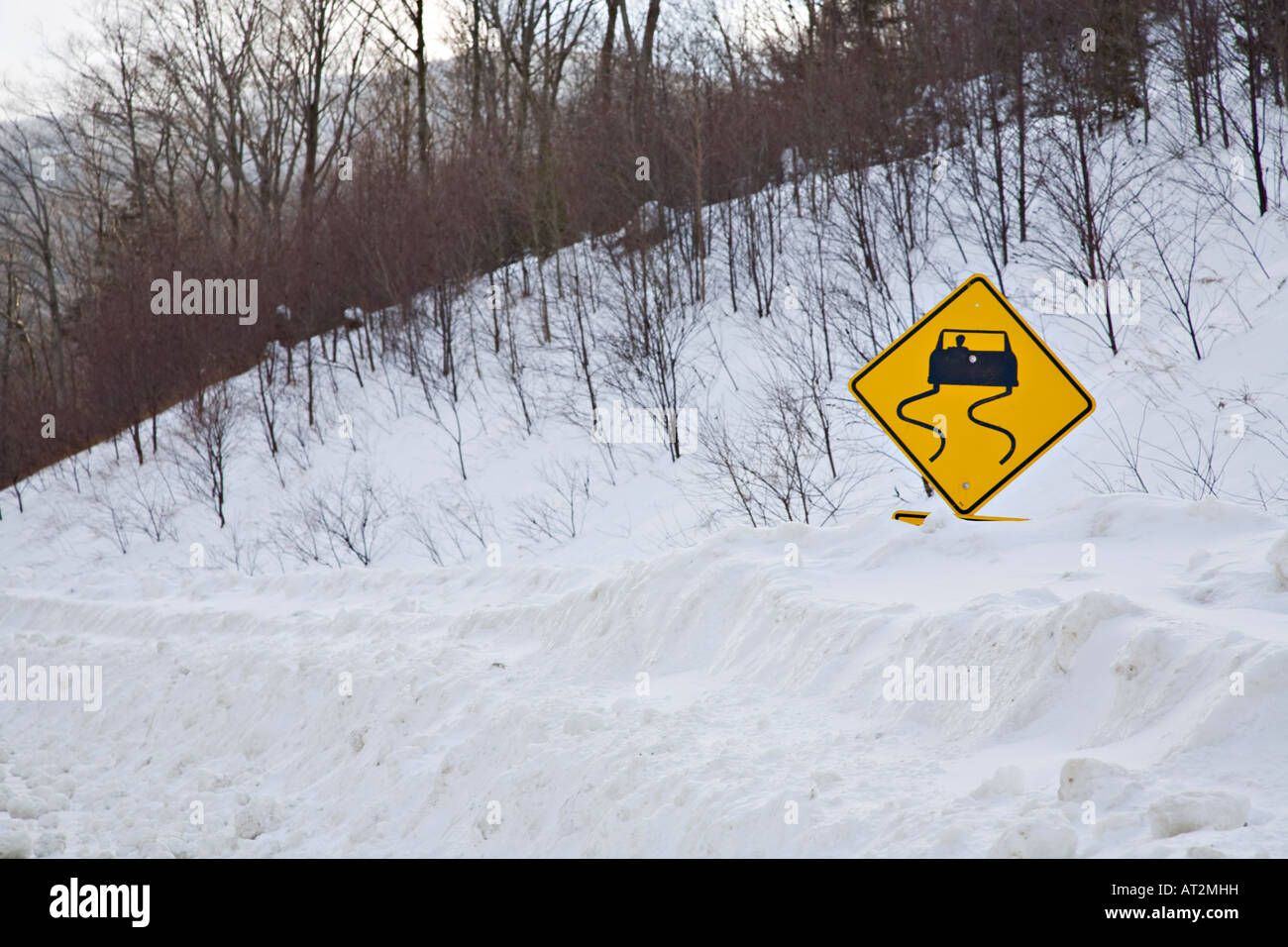 Slippery road sign covered by snow - Stock Image