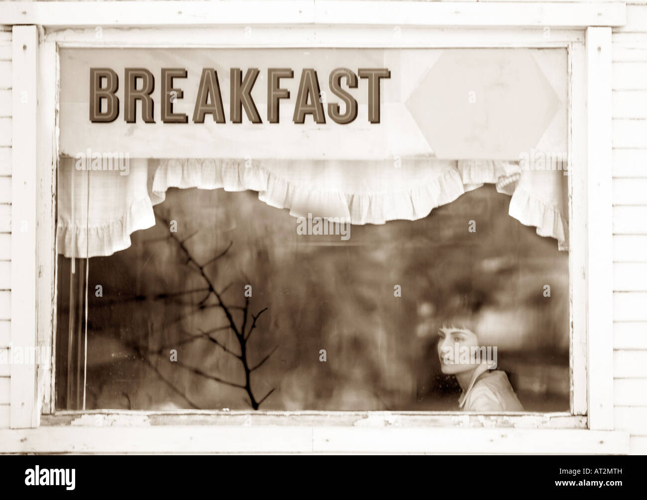 black and white woman with short hair eating breakfast in cafe looks through window with reflections and sign that - Stock Image