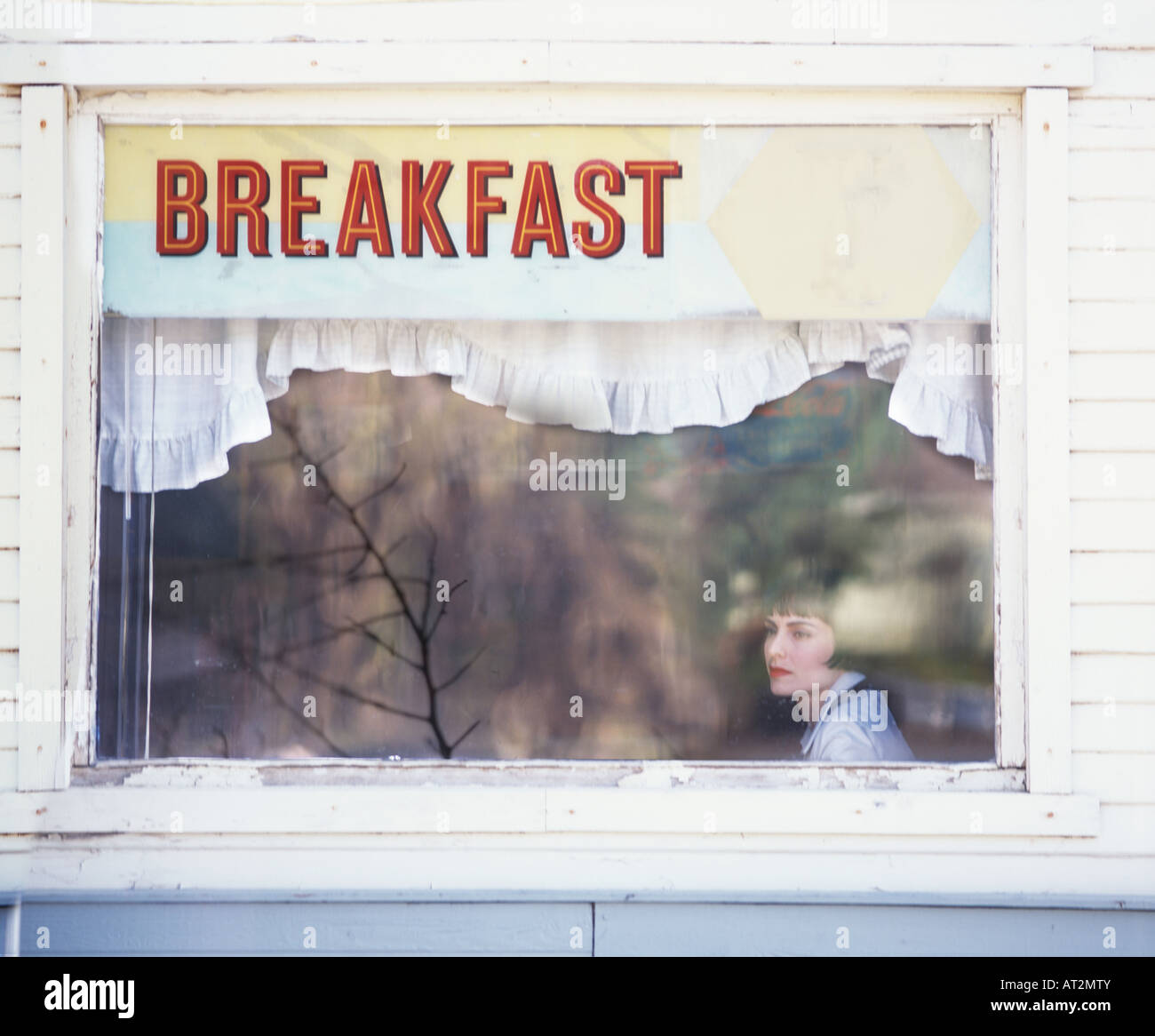 fashionable woman eating breakfast in cafe looks through window with reflections and sign that says breakfast - Stock Image