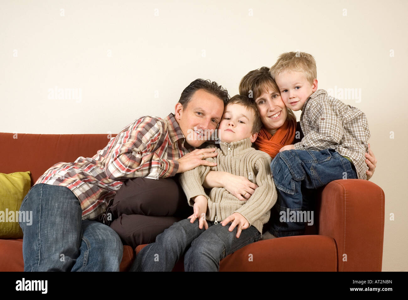 Nice family picture sitting together on a couch - Stock Image