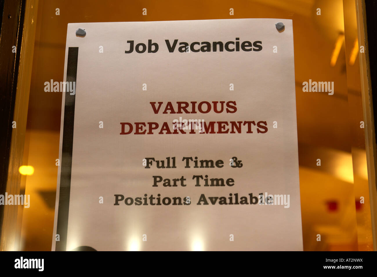 job vacancies notice posted in the window of a pub and hotel at night in tourist pub club area of belfast - Stock Image