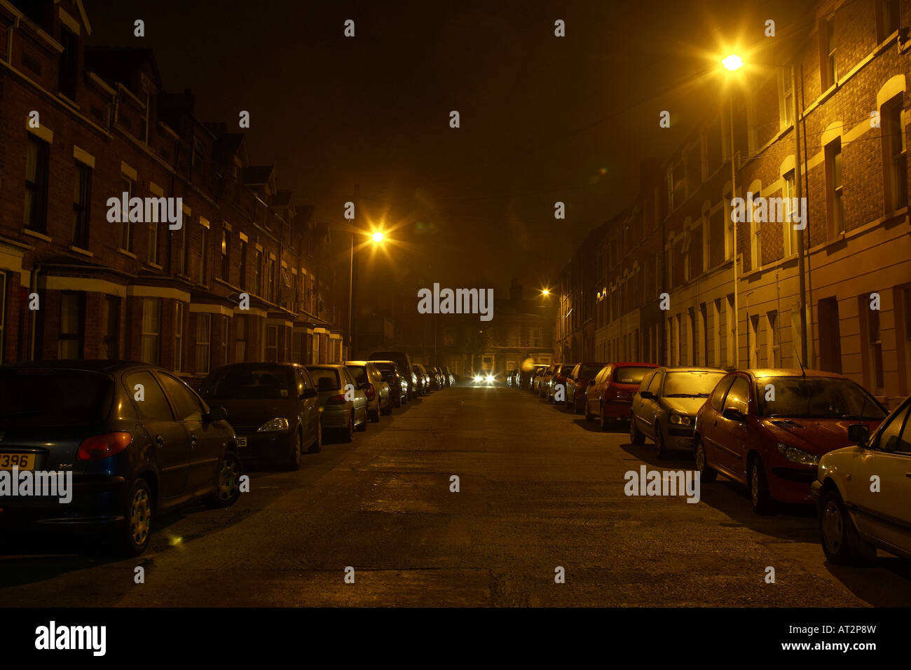 car approaching down the middle of a narrow dark nighttime street in Belfast - Stock Image