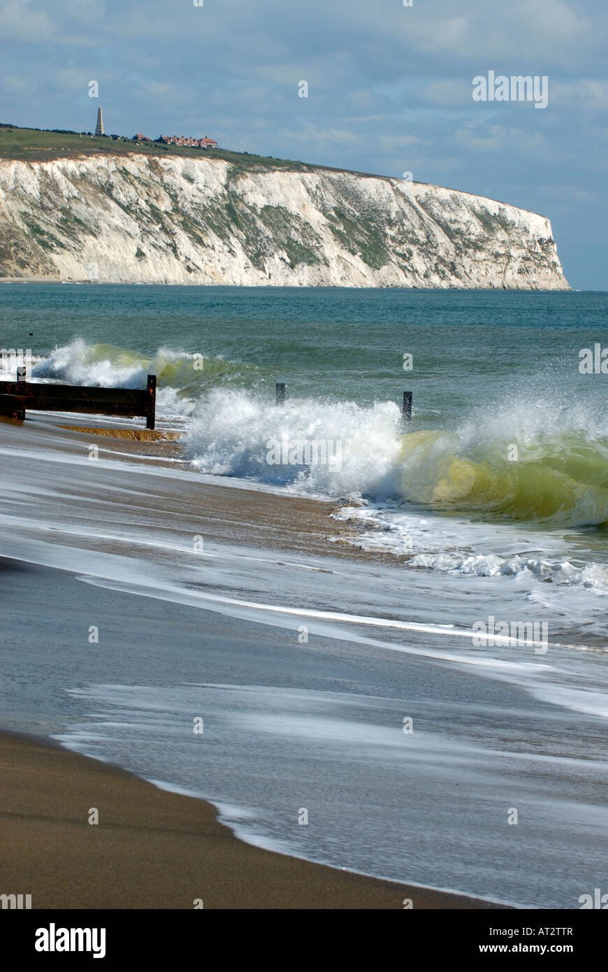 the sandy beach with waves breaking over the groynes and sea defences with cliffs in the background at sandown yaverland - Stock Image