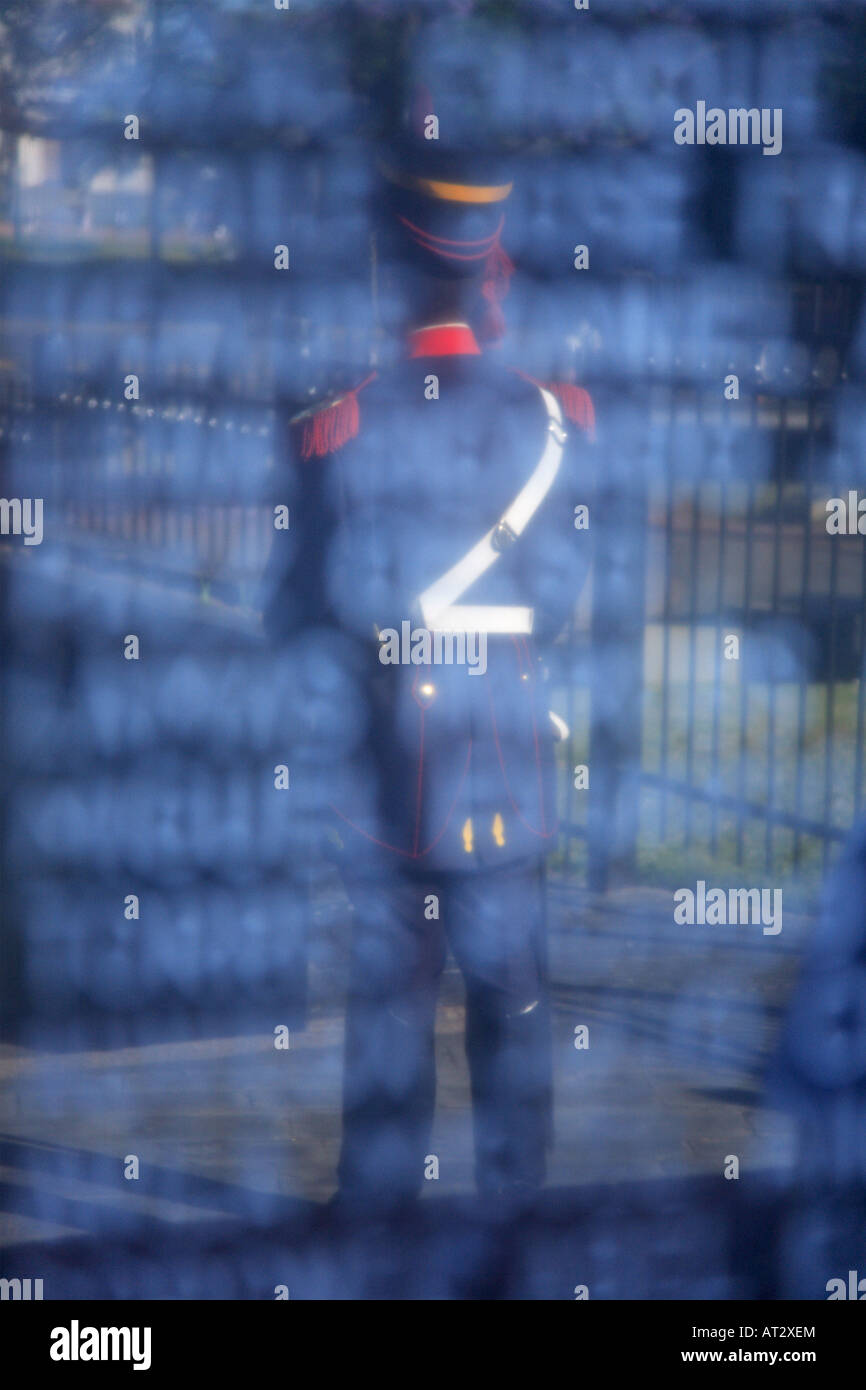 Grenadier traditional soldier in custody of the Monument to fallen soldiers in Faukland conflict, during 1982, reflected - Stock Image