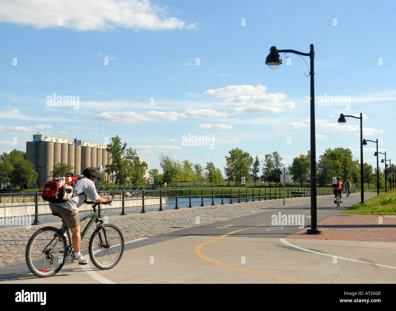 People Cycling next to canal Lachine city of Montreal Province of Quebec Canada - Stock Image