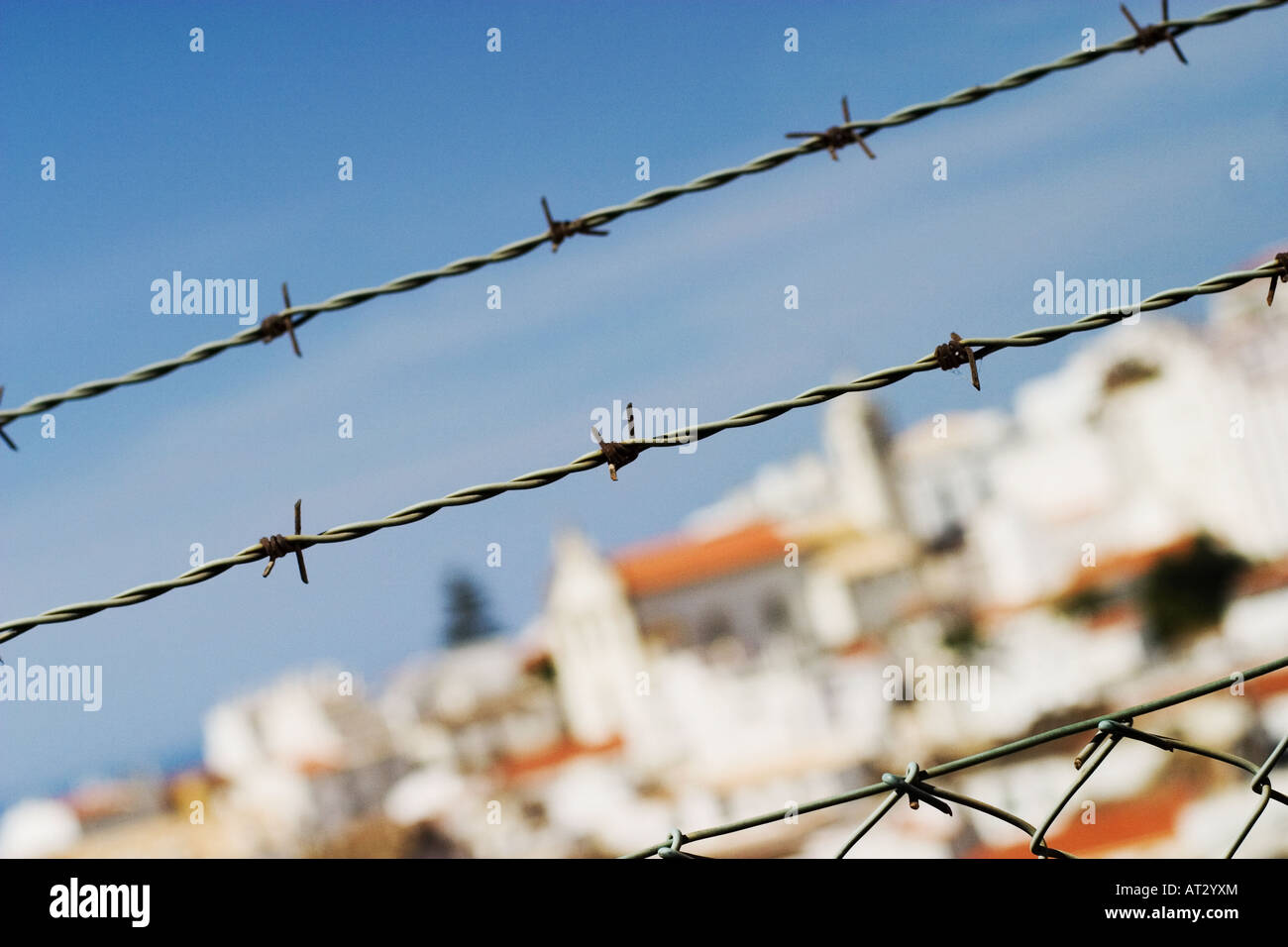 A Barbed Wire fence looking over the white houses in the algarve ...