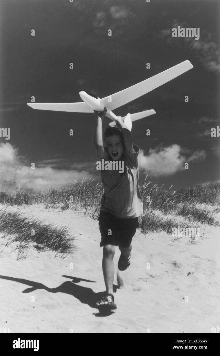 A boy running a long a beach with a model airplane - Stock Image