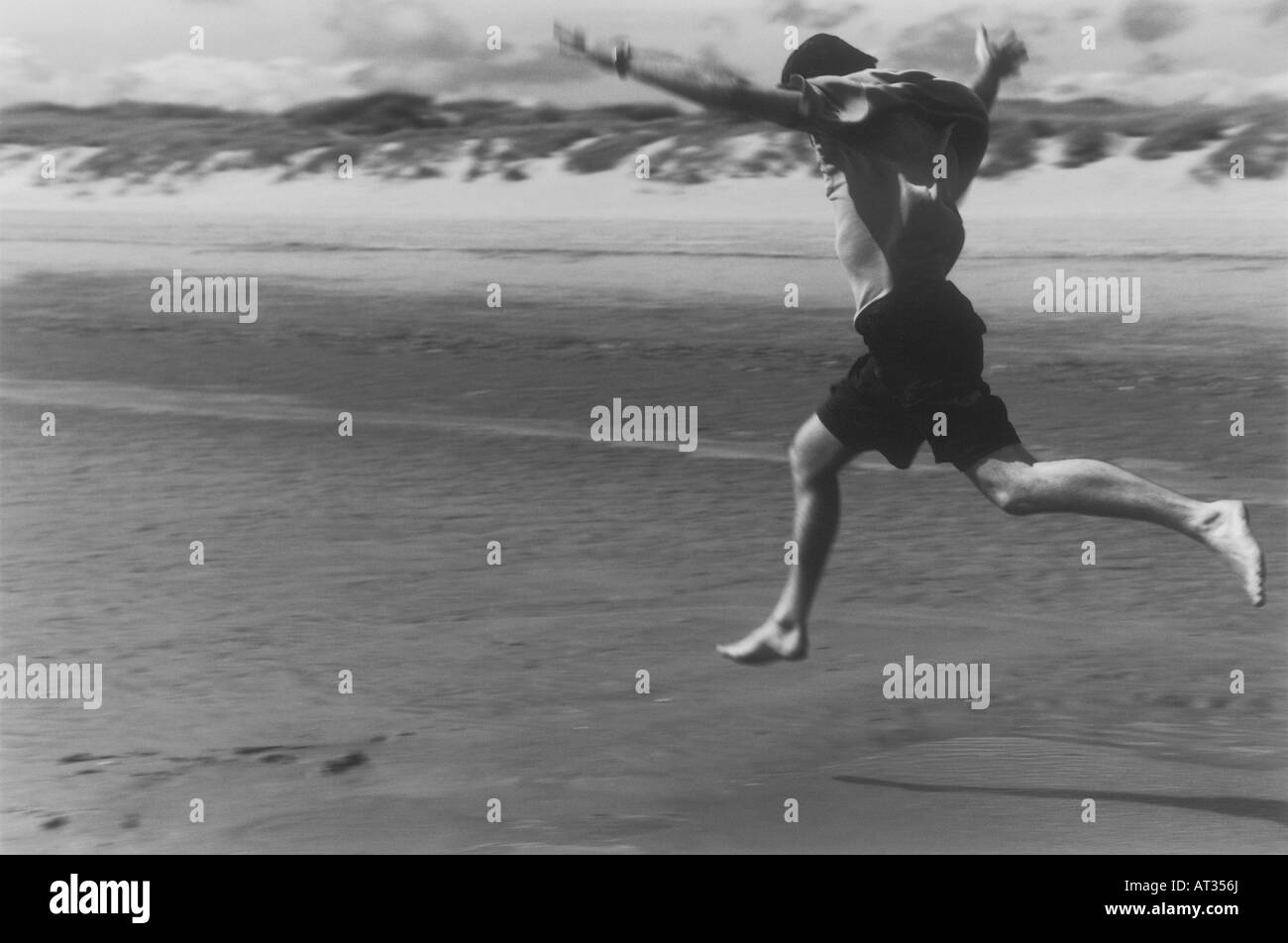 A man running a long a beach, jumping arms stretched out - Stock Image