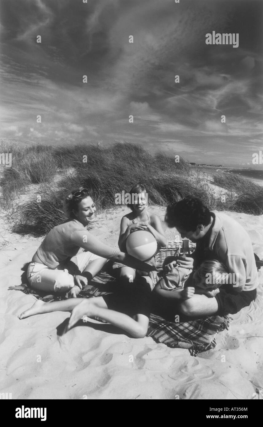 A family having a picnic on a beach - Stock Image