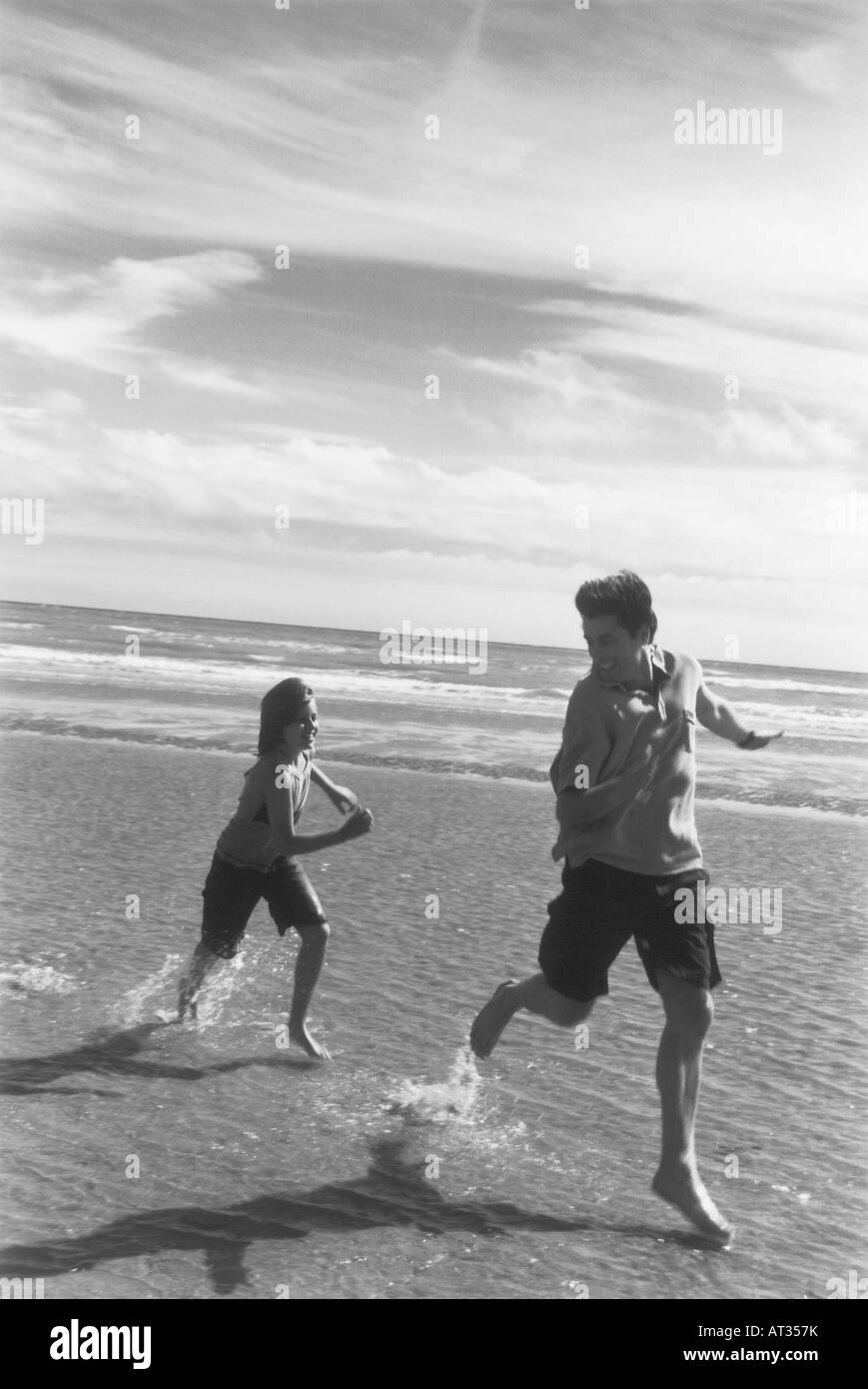 A father being chased along the beach by his daughter Stock Photo
