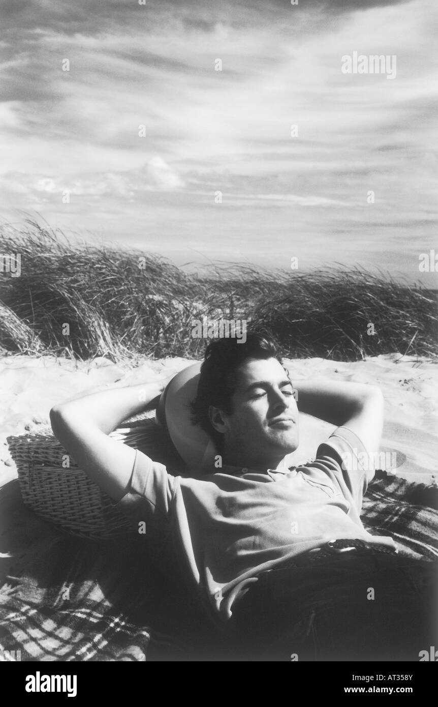 A man lying in the sun, resting on a picnic hamper - Stock Image