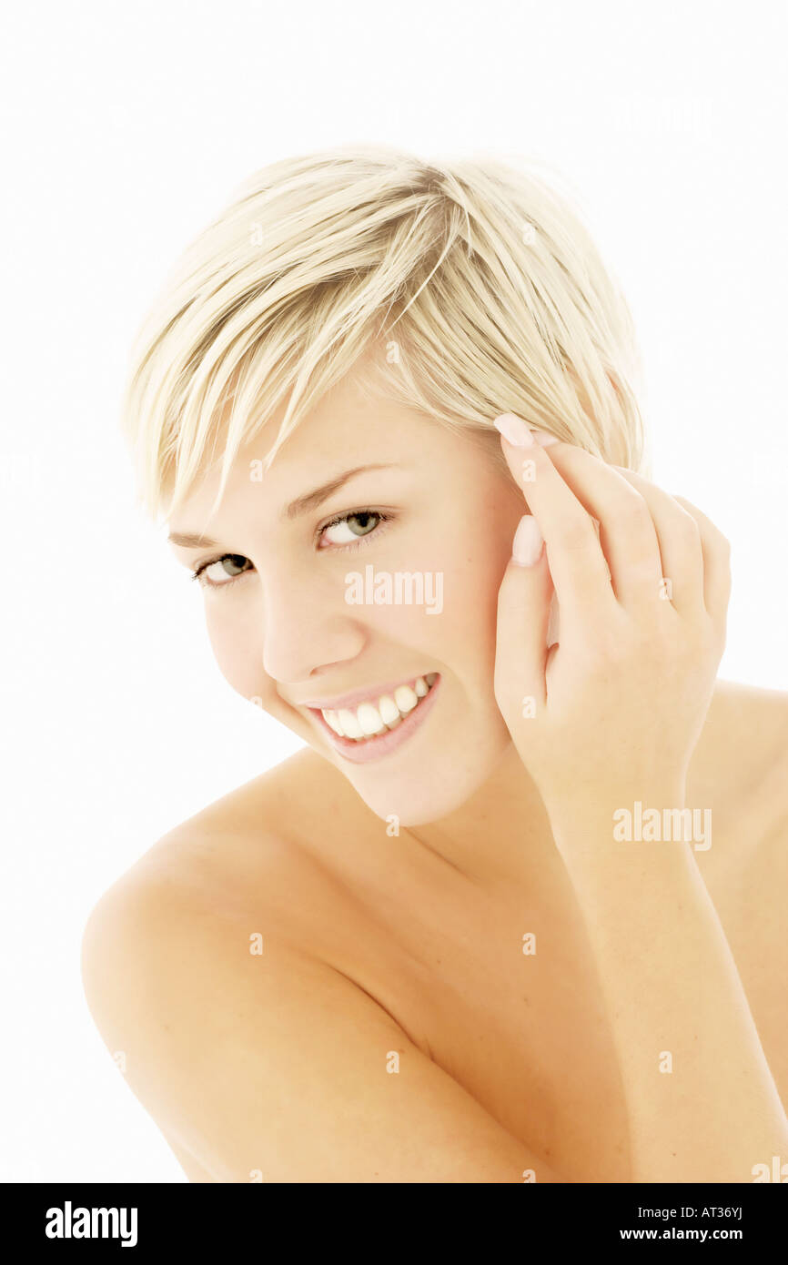 A head and shoulders portrait of a woman, hands to face, towards camera - Stock Image