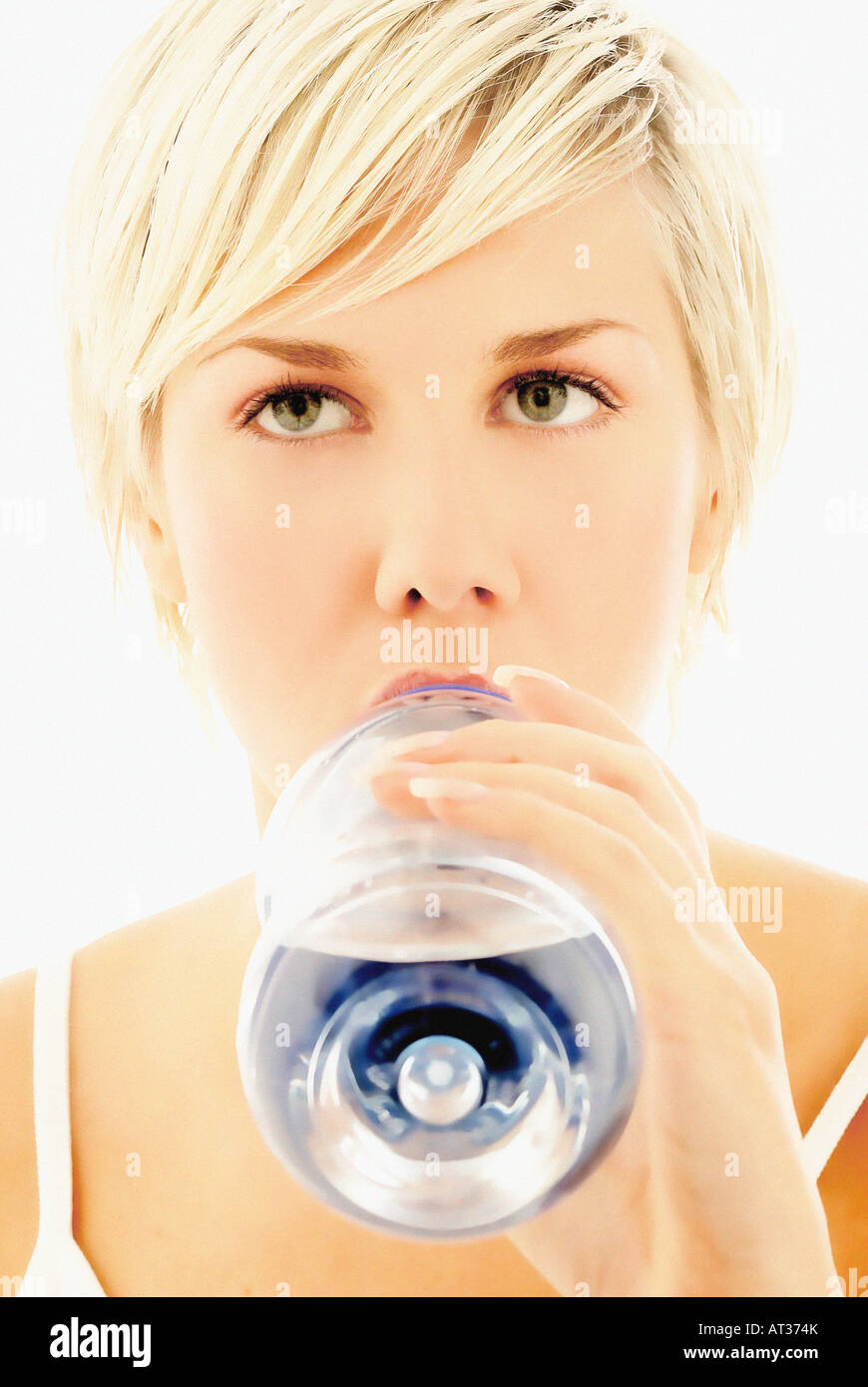 A woman drinking water from a plastic bottle - Stock Image