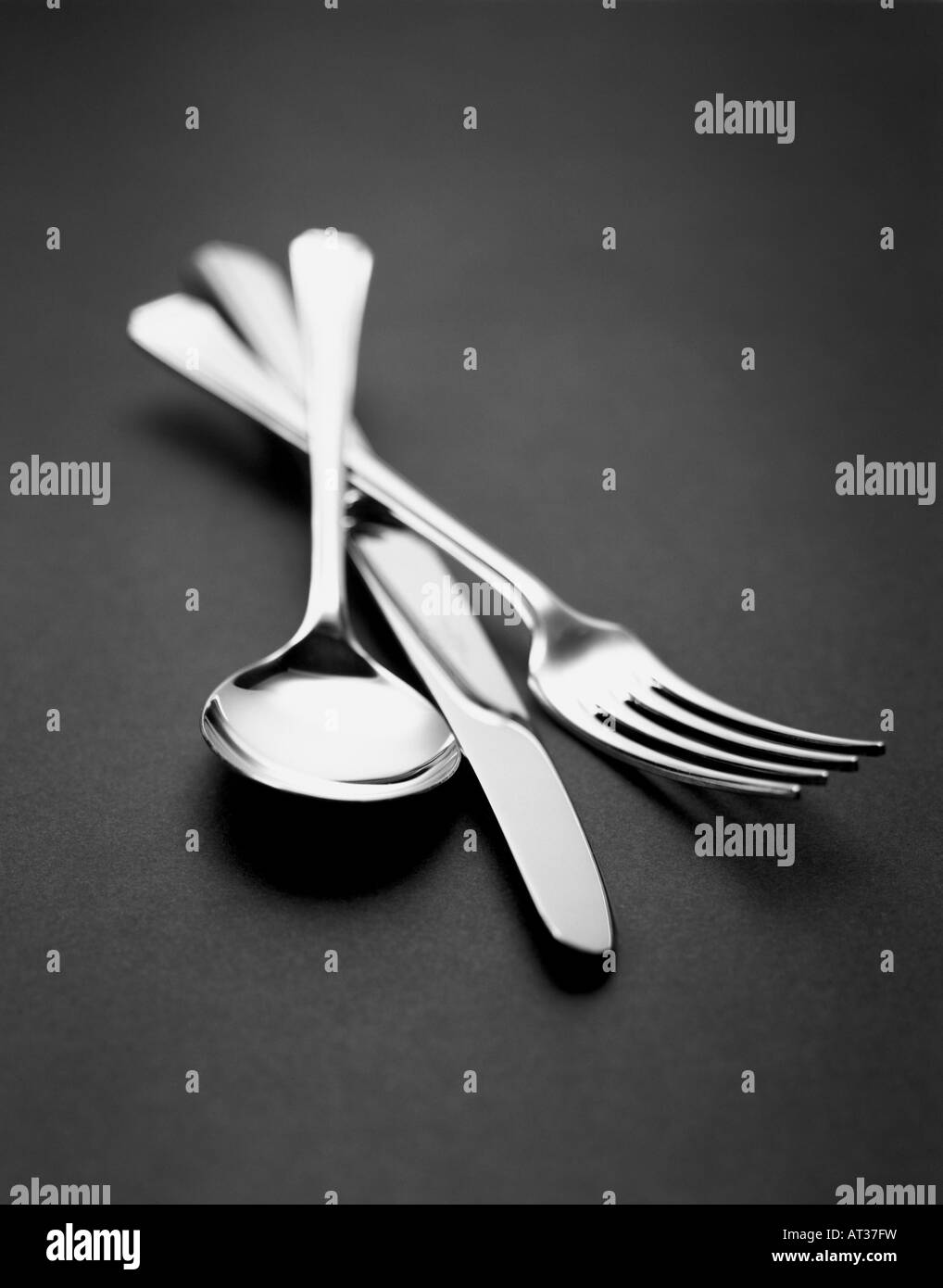 A silver knife, fork and spoon, black and white - Stock Image