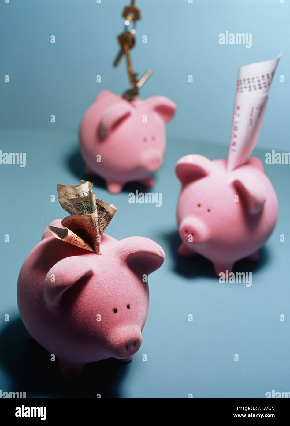 Money, keys and receipts in pink piggy banks Stock Photo