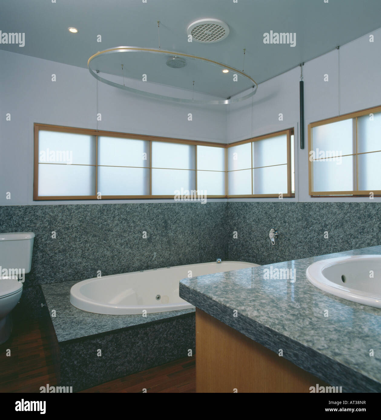 Grey Granite Walls To Dado Height In Modern Bathroom With White Blinds On  Narrow Windows