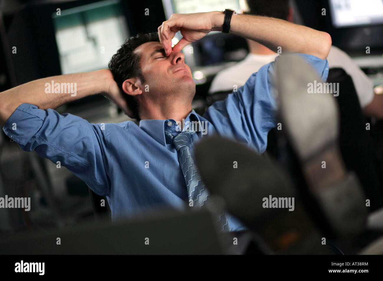 A business man reclining with his feet on his desk, tired - Stock Image