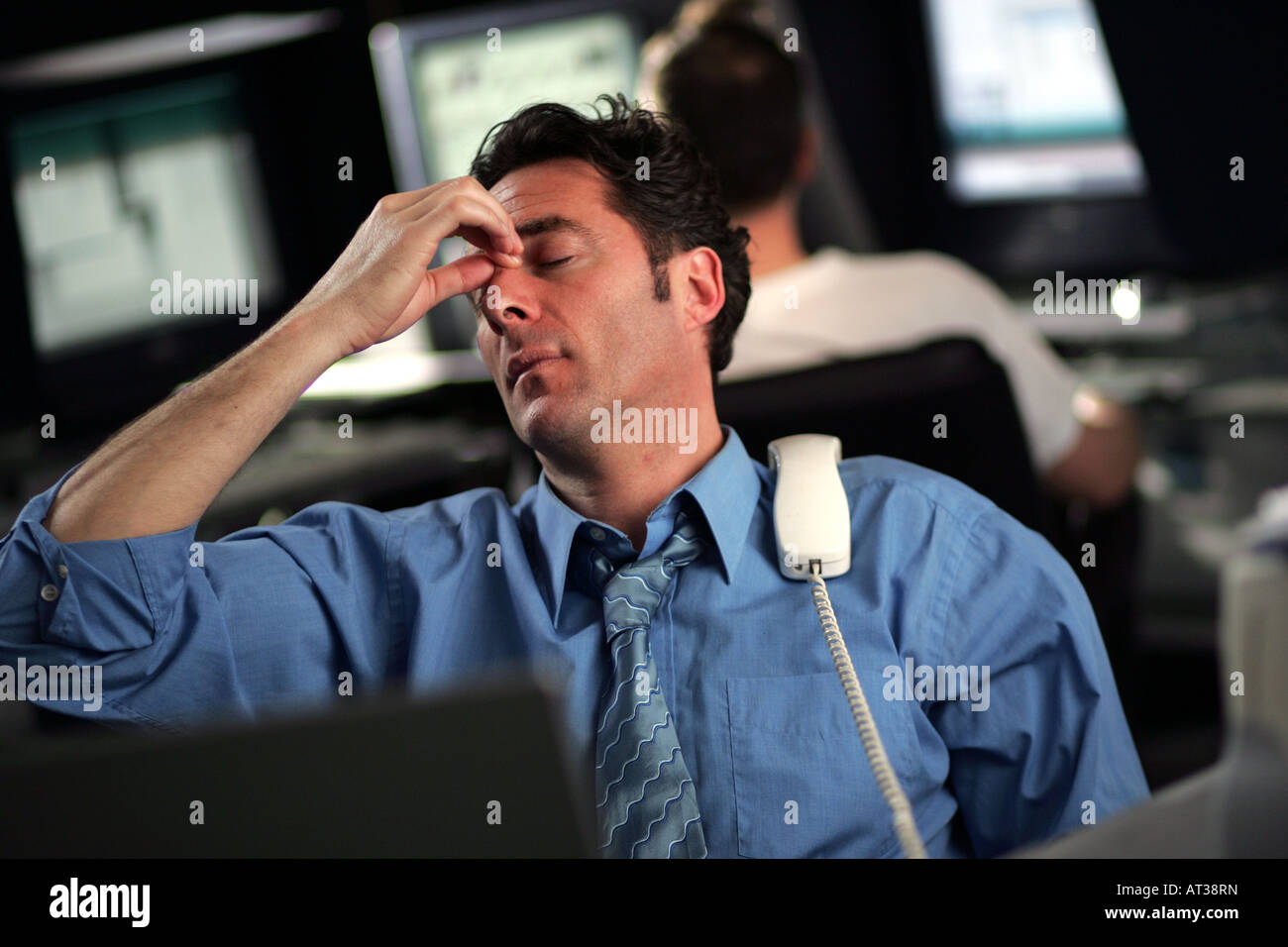 A business man with a phone rested on his shoulder, tired - Stock Image