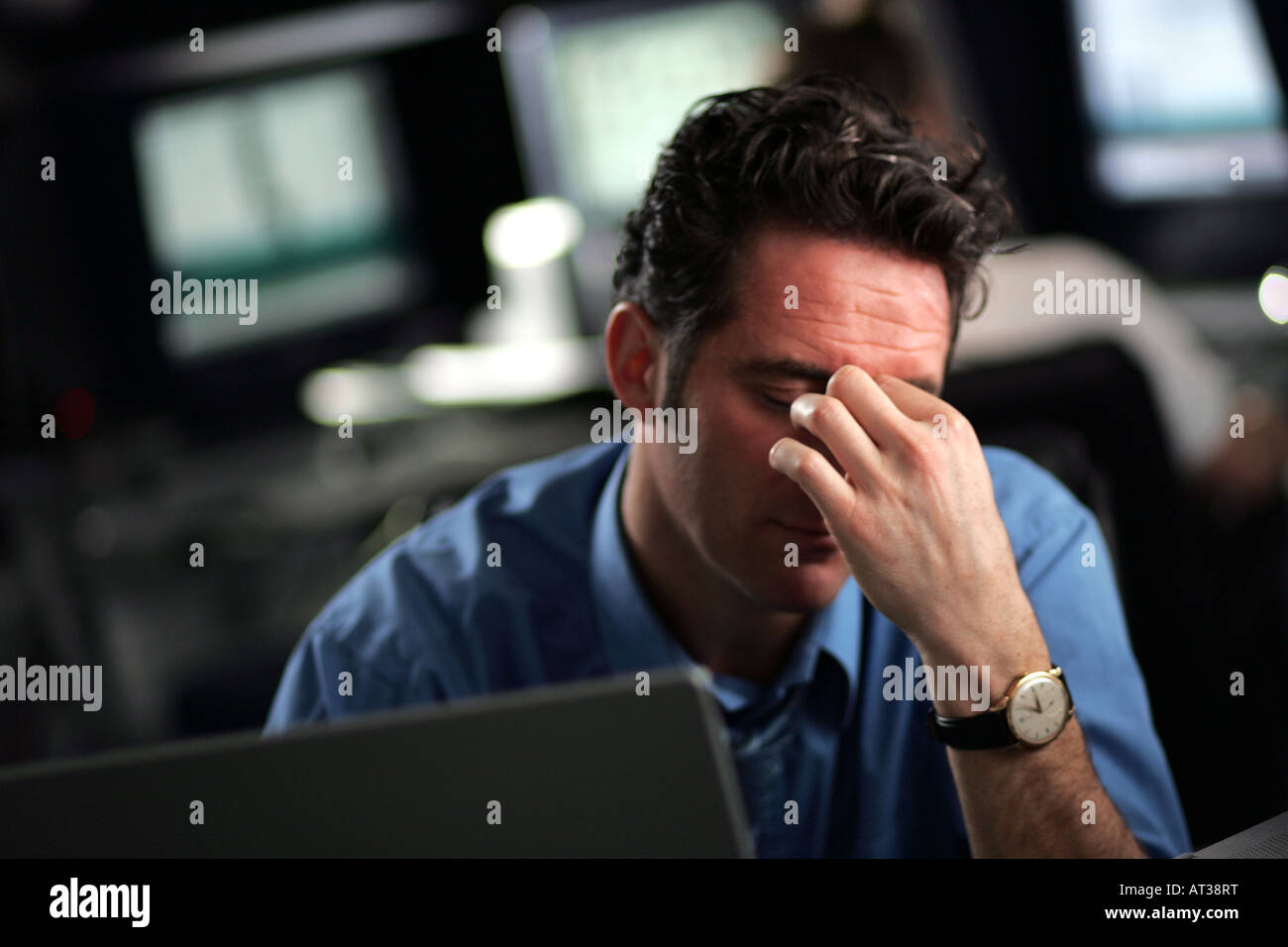 A business man sitting at his desk looking tired - Stock Image