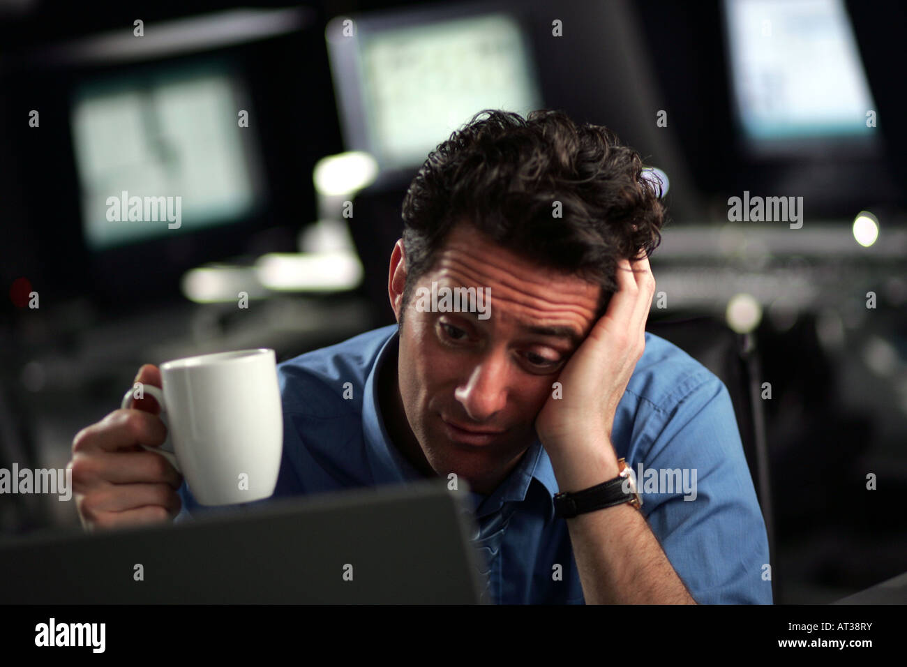 A business man sitting at his desk looking tired holding a cup of coffee - Stock Image