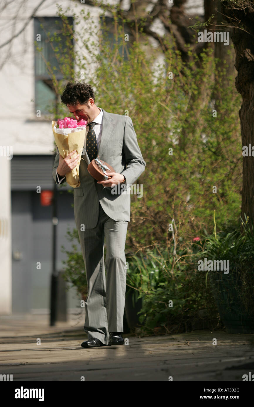 A man smelling a bunch of flowers - Stock Image