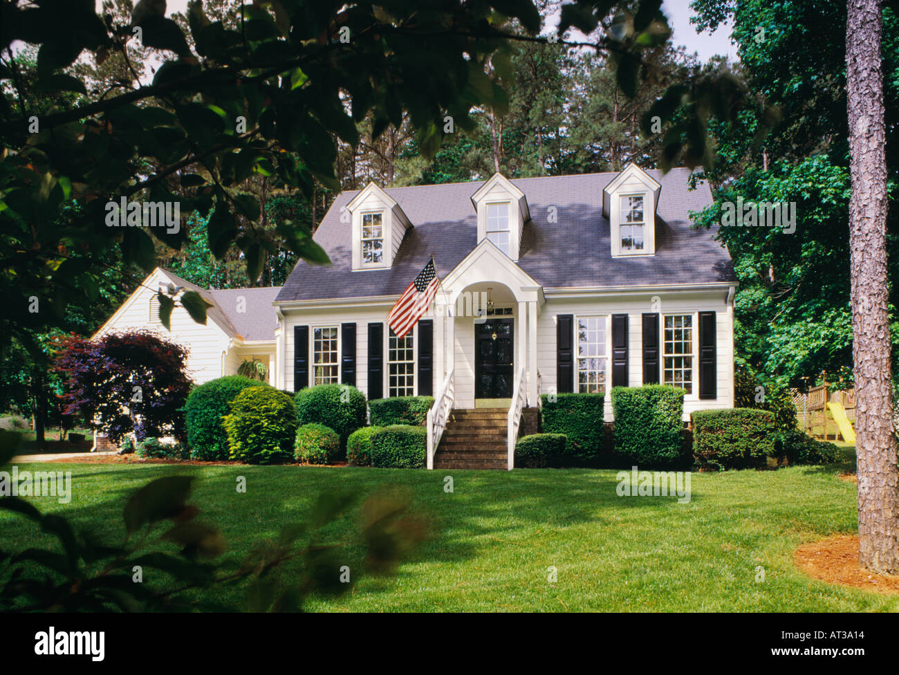 Small White House With Dormers Black Trim And An American Flag Hanging Near  The Front Door