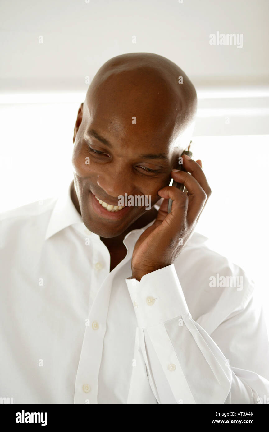A black male wearing a white shirt talking on a mobile phone - Stock Image