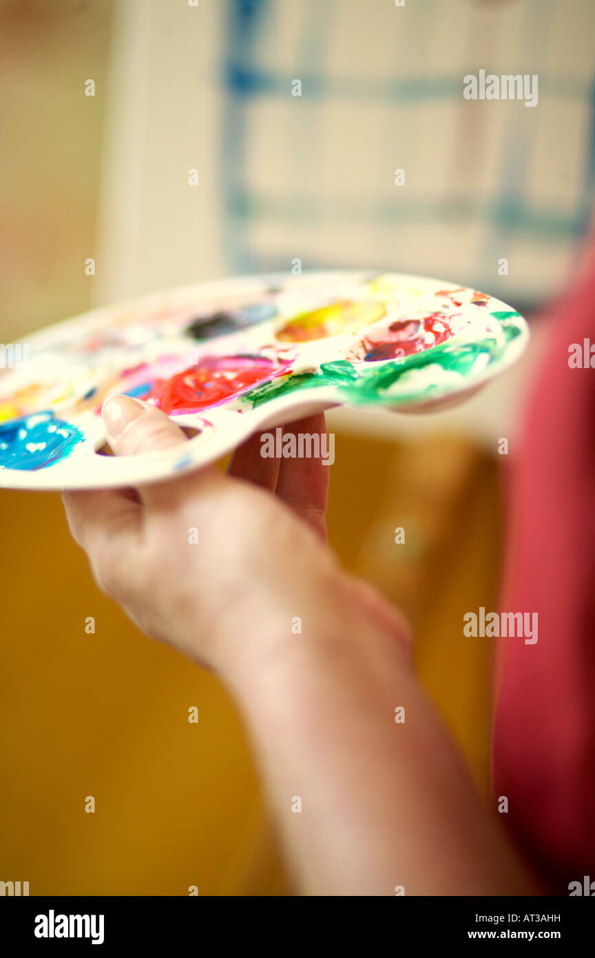 A female artist holding a paint palette, close-up Stock Photo