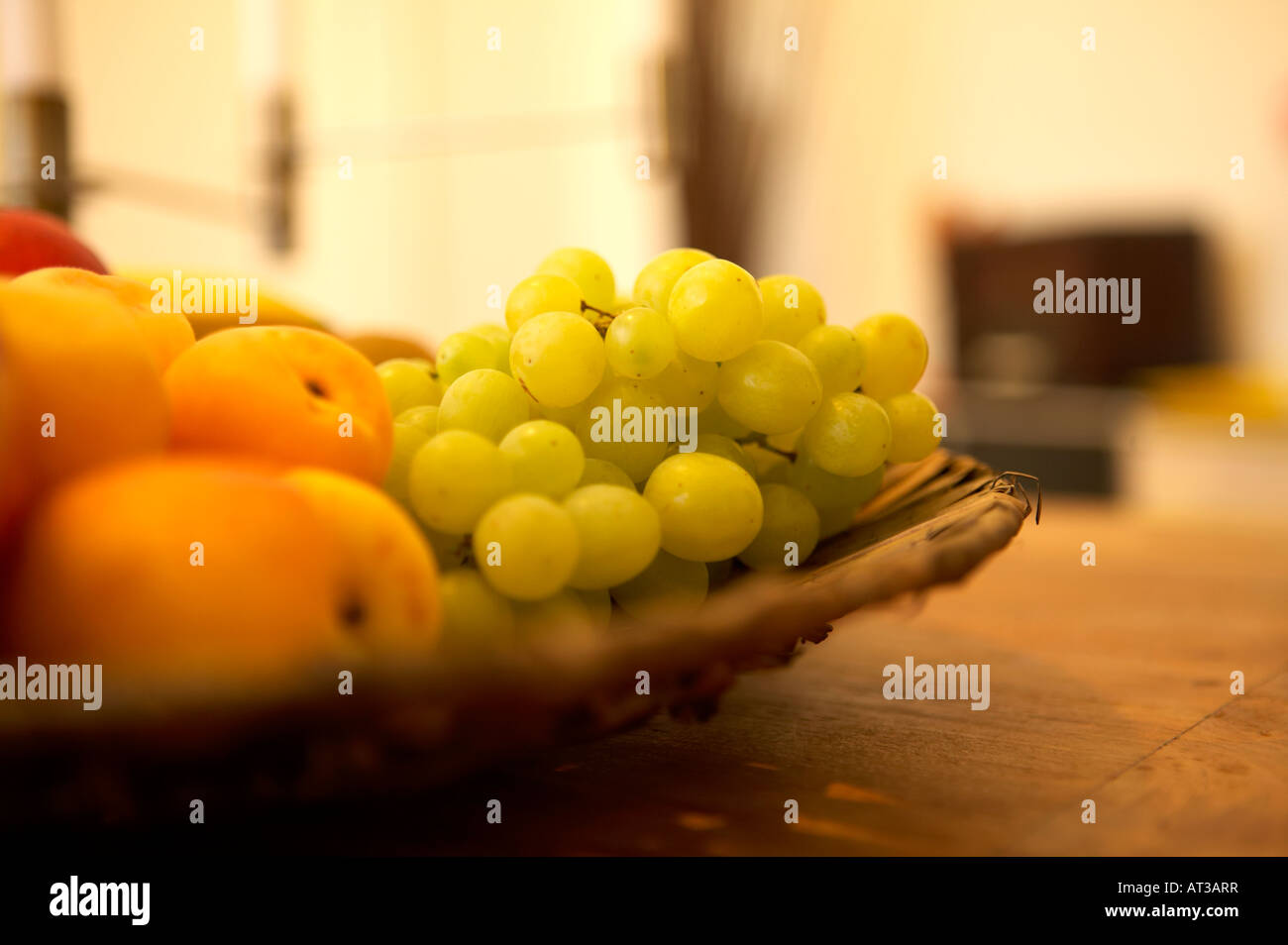 A basket of fruit on a table - Stock Image