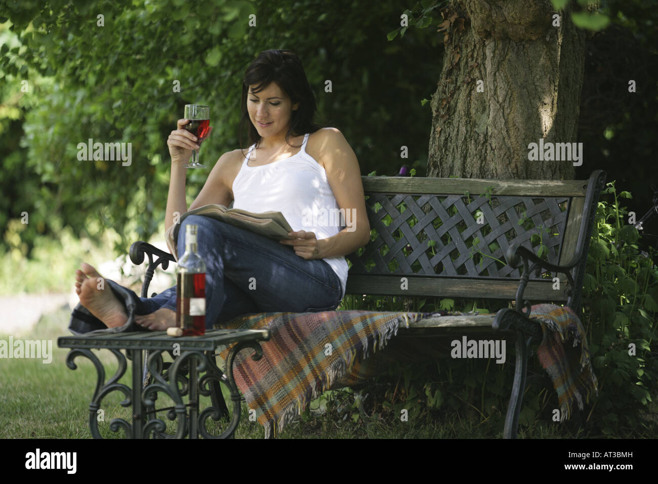 A woman sitting in the garden holding a glass of wine and reading a newspaper - Stock Image