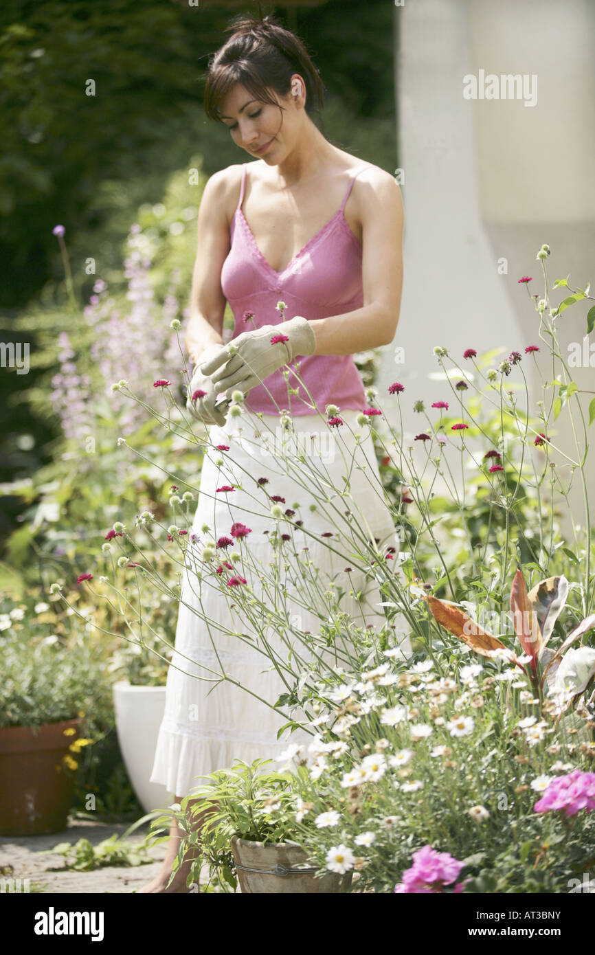 A young woman standing in her garden pruning flowers - Stock Image