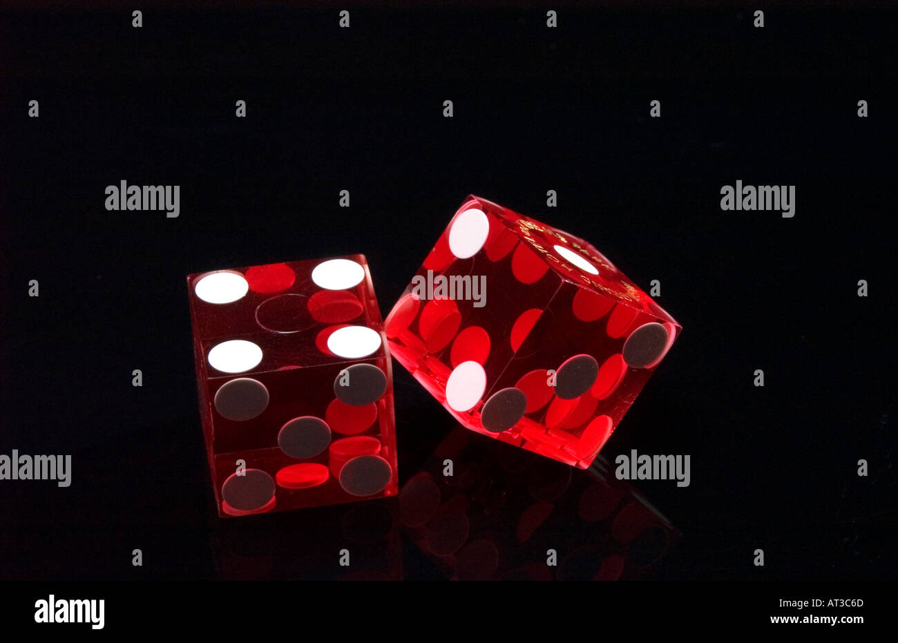 Close up of red casino dice on black reflective background - Stock Image