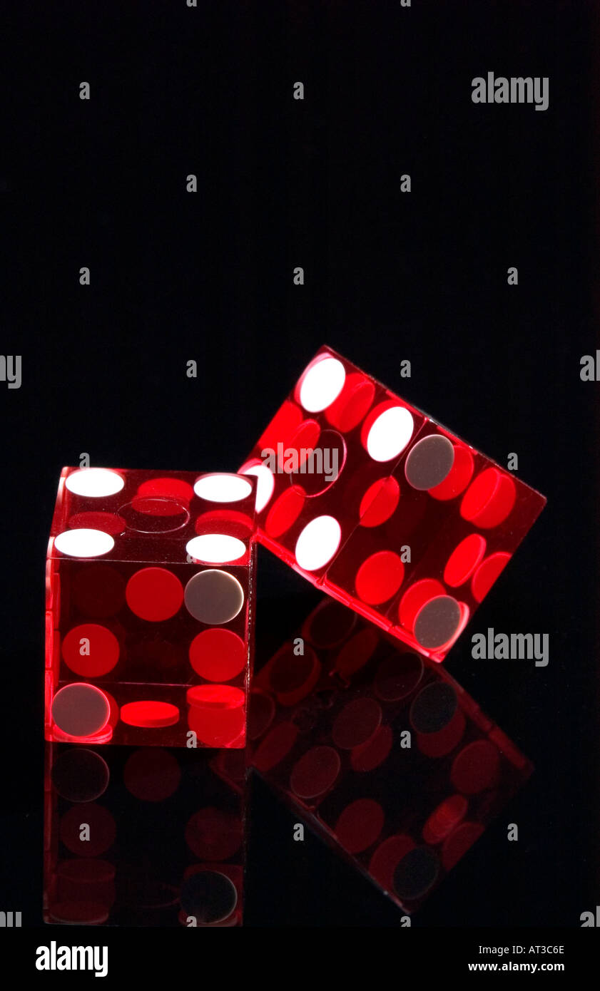 Red casino dice on black reflective background - Stock Image