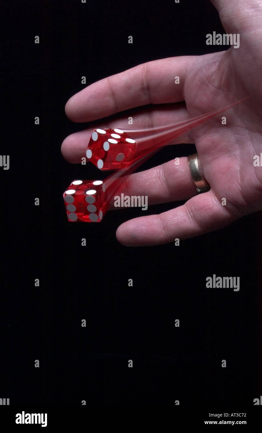 Hand throwing dice with motion trail - Stock Image
