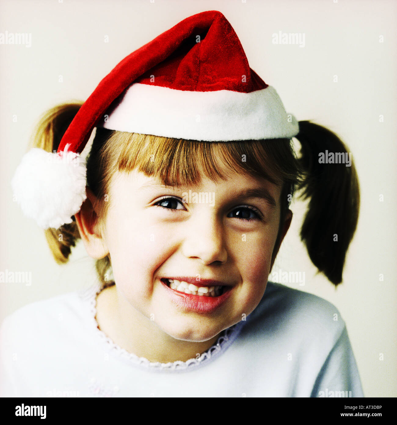 A girl wearing a Santa hat - Stock Image