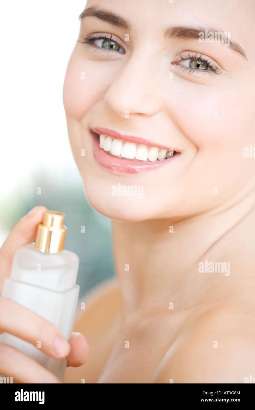 Woman spraying perfume on her neck, smiling - Stock Image