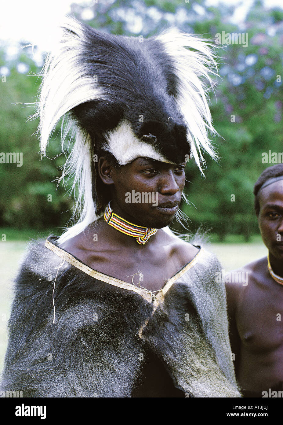 Young black African wearing the traditional skin cape and hat worn by the Laibon of Chief of the Nandi tribe in - Stock Image