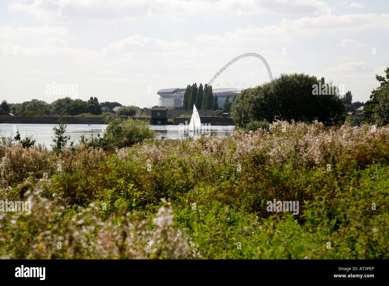 Yacht on Welsh Harp seen in front of Wembley Stadium, London - Stock Image