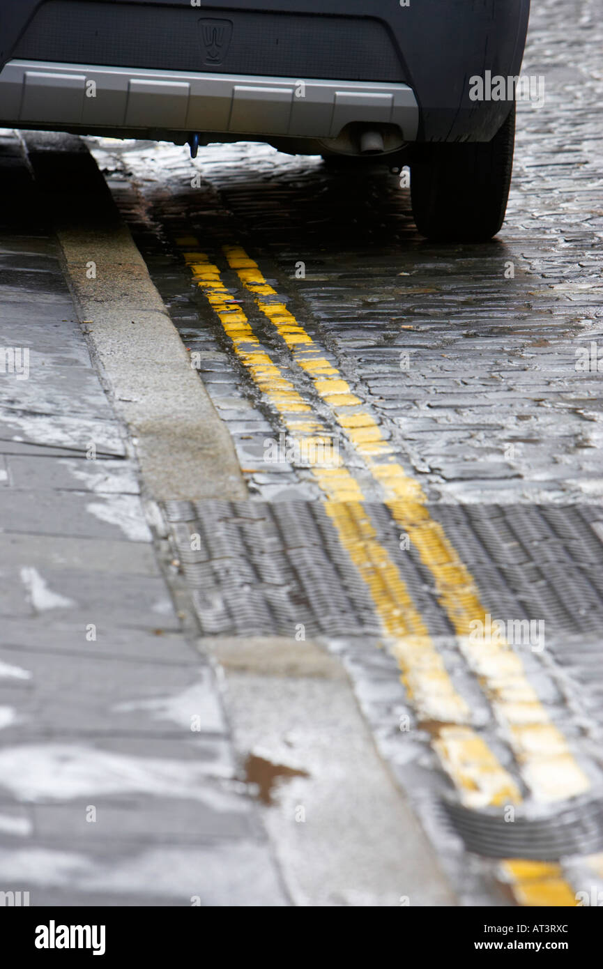 back of car parked on bright double yellow lines no parking road markings on old cobbled street - Stock Image